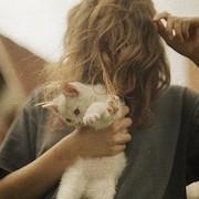 Обнаженна девушка с котенком на пляже.